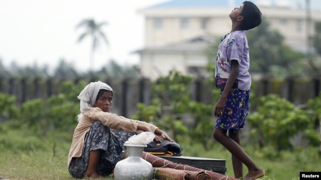 Rohingya Muslims people rest by the road with their belongings as they move from their village after recent violence in Sittwe, June 16, 2012.