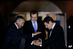 FILE - Cyprus' president Nicos Anastasiades, right, Turkish Cypriot leader Mustafa Akinci, left, and United Nations envoy Espen Barth Eide shake hands after a dinner at the Ledra Palace Hotel inside the U.N.-controlled buffer zone that divides the Cypriot capital Nicosia, May 11, 2015.