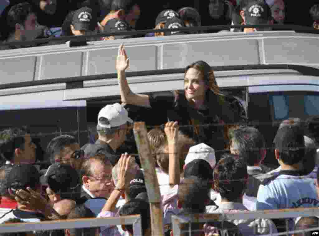 Angelina Jolie, the Hollywood celebrity and goodwill ambassador for the U.N. High Commissioner for Refugees waves as she exits a van surrounded by Syrian refugees at the Altinozu refugee camp near the Syrian border, Friday, June 17, 2011. (AP Photo/Selc