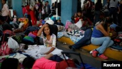 Venezuelan migrants start to wake up after spending the night at the Ecuadorian Peruvian border service center to get their documents processed and continue their journey, in the outskirts of Tumbes, Peru June 15, 2019. (REUTERS/Carlos Garcia Rawlins)