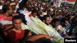 Para pendukung Presiden terguling Mohamed Morsi menggotong rekan mereka yang tewas dalam bentrokan dengan militer Mesir (8/7).