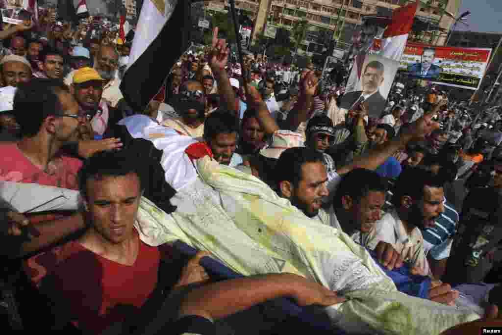 Supporters of Egypt's deposed President Mohamed Morsi carry the body of a fellow supporter killed by violence outside the Republican Guard headquarters in Cairo, July 8, 2013.