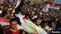 穆尔西的支持者7月8日抬着遇难者尸体示威