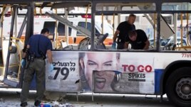 Israeli police officers examine a damaged bus at the site of a bombing in Tel Aviv, Israel, November 21, 2012.