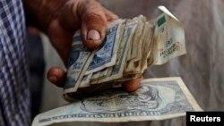 지난 12일 쿠바 중부 사구아라그란데의 한 시장에서 상인이 돈을 세고 있다.