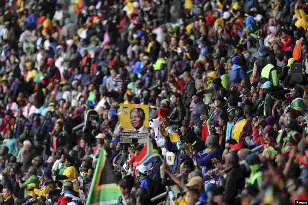 A man holds a placard with an image of Nelson Mandela at the FNB Stadium during a national memorial service, Dec. 10, 2013.