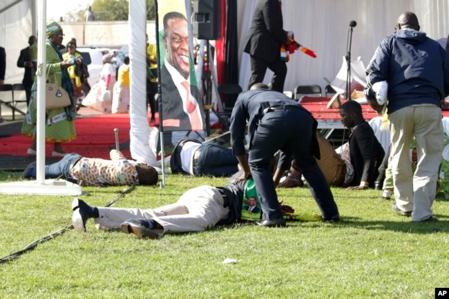 FILE - Injured people lay on the ground following an explosion at a ZANU-PF rally in Bulawayo, June, 23, 2018.