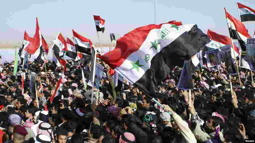 Sunni Muslims wave the old flag of Iraq during an anti-government demonstration in Ramadi, Iraq, December 26, 2012.