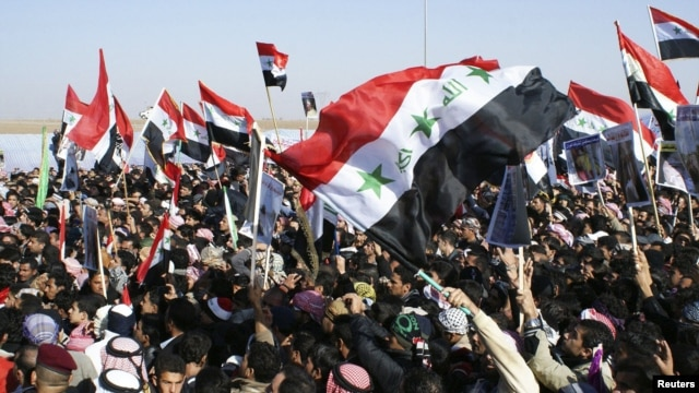 Iraqi Sunni Muslims wave the old flag of Iraq during an anti-government demonstration in Ramadi, 100 km (62 miles) west of Baghdad, December 26, 2012.