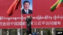 Seorang perempuan menyiram taman di depan papan ucapan selamat datang untuk Presiden China Xi Jinping, di Naypidaw, Myanmar, 17 Januari 2020. (Foto: AFP)