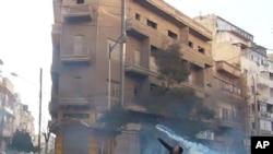 一名示威抗議者27日在敘利亞城市霍姆斯拋出一個催淚彈。