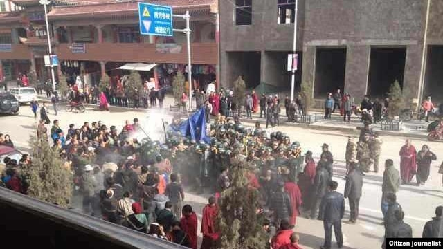 Citizen journalist image shows crowds surrounding Dorjee Rinchen, a Tibetan man who self-immolated in Labrang, China, October 23, 2012.