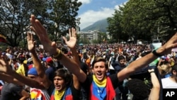 Protesting students shout slogans against Venezuela's President Nicolas Maduro in Caracas, Venezuela, Friday, Feb. 14, 2014. Students are protesting the Wednesday killings of two university students who were shot in different incidents following an anti-g