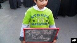 """叙利亚男孩儿拿着的黑板上写着""""停止杀人"""""""