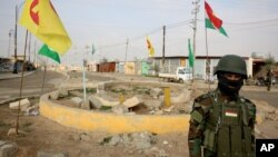 FILE - A soldier of the Kurdish Democratic Party (KDP) patrols at a destroyed roundabout in the town of Snuny, close to Sinjar, northern Iraq, Jan. 29, 2015. The KDP has been using crossings at the Iraq-Syria border as a tool to exert political pressure on its historical rivals that dominate the Syrian Kurdish region.