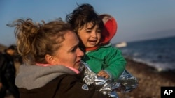 A volunteer holds a baby after her family's arrival on a dinghy from the Turkish coast to the northeastern Greek island of Lesbos on Nov. 17, 2015.