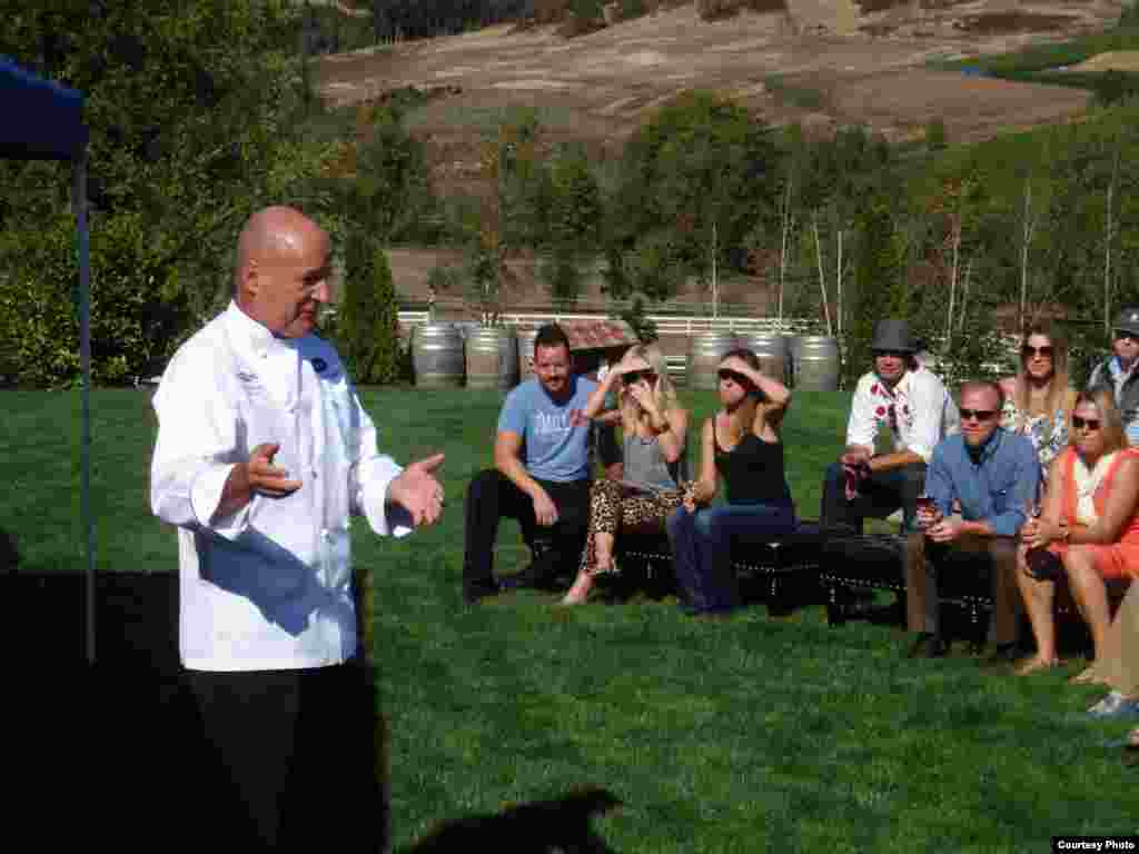 Chef Philippe Parola speaks to attendees at a Eradication by Mastication dinner at Zenith Vineyard. (Tom Banse)
