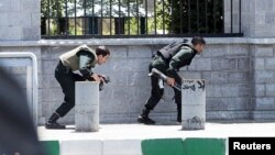 FILE - Members of Iranian forces take cover during an attack on the Iranian parliament in central Tehran, Iran, June 7, 2017.