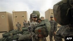 United States Army soldiers load trucks as they begin their journey home to their base in Texas.