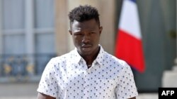 FILE - Mamoudou Gassama, 22, from Mali, leaves the Elysee Palace after his meeting with French President Emmanuel Macron, in Paris, France, May 28, 2018.