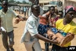 Men carry a woman who passed out as heavy gunfire was directed towards the Baya Dombia school where voters had gathered to cast ballots in a constitutional referendum, in Bangui, CAR, Dec. 13, 2015.