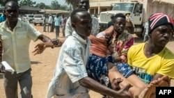 Des hommes portent une femme qui s'est évanouie pendant un échange des tirs à Baya Dombia, Bangui, RCA,13 décembre 2015.