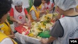 27일 중복을 맞아 하나원 교육생들과 적십자사 회원들이 쪽방촌 주민들에게 삼계탕을 나눠주는 봉사활동을 했다. 참가자들이 삼계탕과 함께 먹을 김치를 만들고 있다.