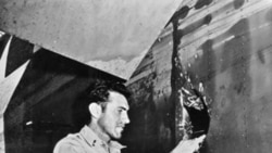 Louis Zamperini shows the hole in his airplane