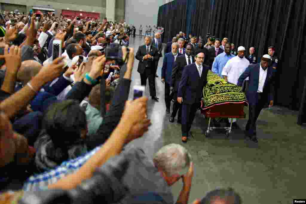Worshipers and well-wishers take photographs as the casket with the body of the late boxing champion Muhammad Ali is brought for his jenazah, an Islamic funeral prayer, in Louisville, Kentucky, USA.