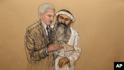 In this photo of a sketch by courtroom artist Janet Hamlin and reviewed by the U.S. Department of Defense, Khalid Sheikh Mohammed consults with his civilian attorney David Nevin during a break of his military hearing at the Guantanamo Bay U.S. Naval Base