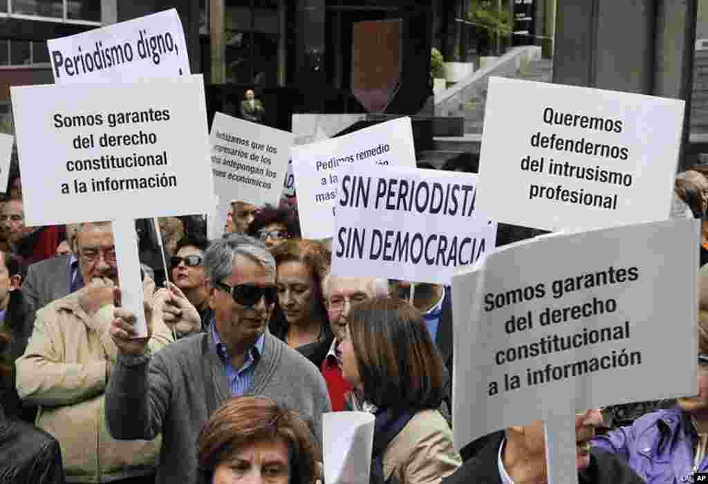 Các nhà báo cầm những tấm bảng với hàng chữ 'Chúng tôi lành người đảm bảo quyền thông tin hiến định' và 'Không có dân chủ nếu không có báo chí' trong một cuộc bầu cử kỷ niệm Ngày Tự do Báo chí Thế giới 3 tháng 5, 2012 tại Madrid. (AFP)