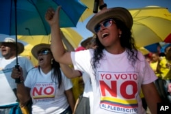 "Demonstrators yell ""No to the plebiscite"" to protest the government's peace agreement with the Revolutionary Armed Forces of Colombia (FARC), to be signed later in the day in Cartagena, Colombia, Sept. 26, 2016."