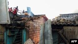 Des gens sur un toit tentant de combattre un incendie qui s'est déclaré sur le marché de Bouaké, dans le centre de la Côte d'Ivoire, le 27 août 2019. (Photo by STR / AFP)