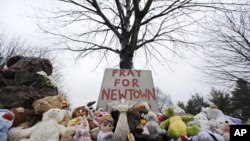 Stuffed animals and a sign calling for prayer rest at the base of a tree near the Newtown Village Cemetery in Newtown, Conn., Dec. 17, 2012.