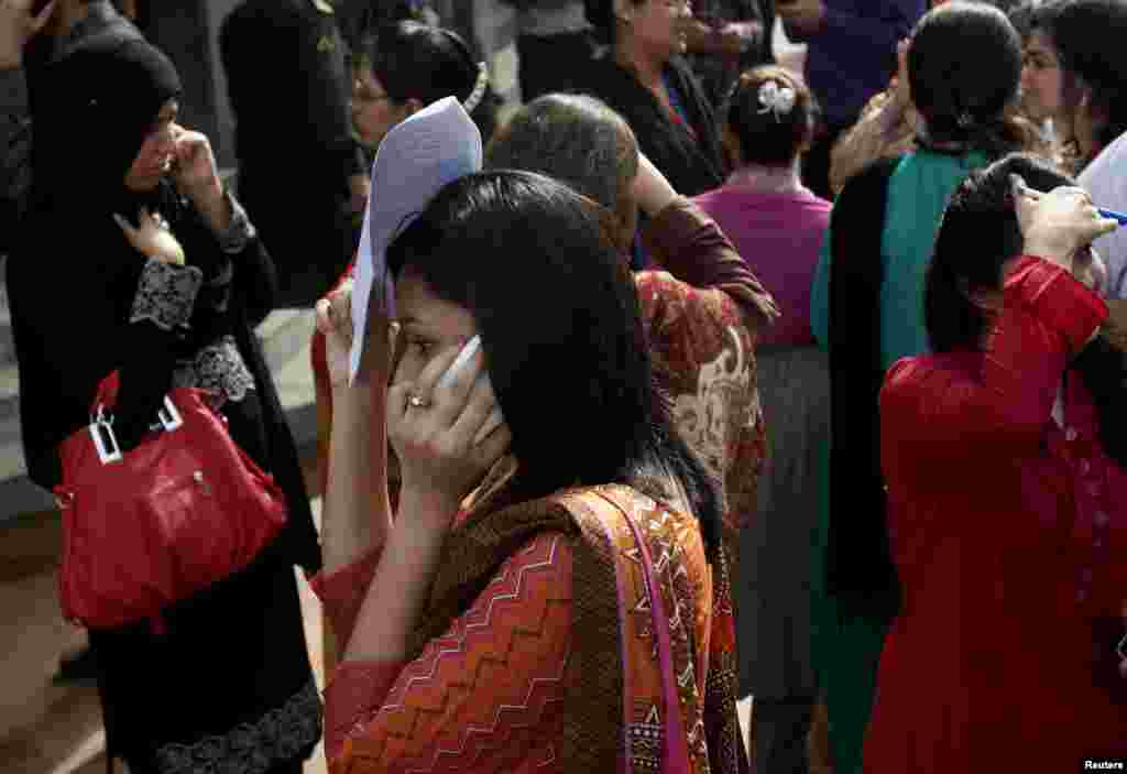 People evacuate buildings and call their relatives after a tremor of an earthquake was felt in Karachi, Pakistan, Tuesday, April 16, 2013.