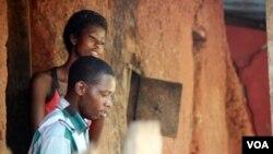 Aid worker Soloman Okoduwa (front) and resident Joy Joy Eriamentor (behind) listen to Naomi Benjamin tell her story. (VOA/Heather Murdock)