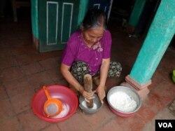 Cụ Sáp giã gạo tẻ để làm bánh chim cò. (Hình: Trịnh Bách)