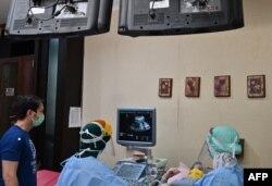 Dokter kandungan Ika Sri Purnamaningsih (tengah) menggunakan alat pelindung diri memeriksa seorang ibu hamil di RSIA Tambak, Jakarta, di tengah pandemi virus corona, 22 April 2020.