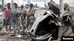 "Officers stand by the remains of a wrecked car at the scene of car bomb explosion along the ""Kilometre 4"" road junction, south of the capital Mogadishu, Somalia, May 5, 2013."