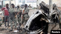 """索马里官员2013年5月5日站在首都摩加迪沙以南""""千米4""""路口发生汽车炸弹爆炸事件现场的汽车残骸旁边"""