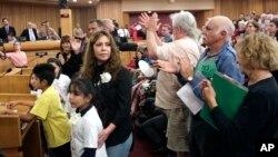 Nora Sandigo Otero and several children under her legal guardianship receive a standing ovation upon their arrival at a Miami-Dade County immigration hearing, Feb. 17, 2017, in downtown Miami. Sandigo Otero is asking Miami-Dade commissioners to reverse Mayor Carlos Gimenez's position on immigration that requires local police to work with federal officers to enforce immigration law.