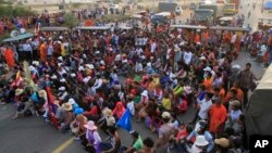 Cambodian garment workers and villagers block the main road demanding freedom for some worker activists who were arrested during Thursday's strike in Kambol village, on the outskirts of Phnom Penh, Cambodia, Thursday, Jan. 2, 2014. Troops have been used t