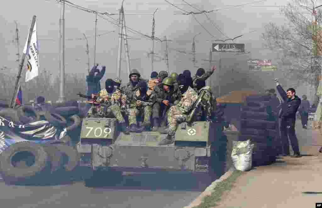 A combat vehicle with gunmen on top makes its way through a checkpoint to the town of Slovyansk, Ukraine, April 16, 2014.