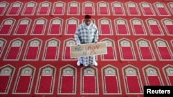 "FILE - Muslim Khaloar Abdarahim holds a placard which reads ""Not in my name"" as he poses inside the Arrahma Mosque after Friday prayers in Nantes, western France, Sept. 26, 2014 after a gathering to pay tribute to French mountain guide Herve Gourdel who was beheaded by an Algerian Islamist group."