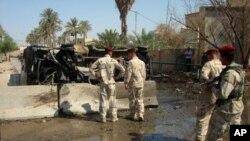 伊拉克士兵检查6月21日在迪瓦尼耶发生炸弹袭击的现场