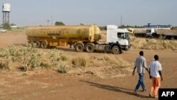FILE - Two men walk near the Paloch oil fields in Upper Nile State, the site of an oil complex and key crude oil processing facility in the north of the country near the border with Sudan.