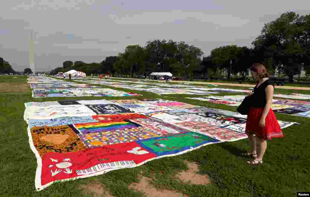 A woman looks out over the AIDS Memorial Quilt, which is now in its 25th year, on the National Mall in Washington July 24, 2012.