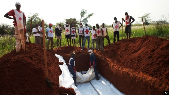 Workers from the Central African Red Cross bury 13 victims of sectarian violence in a mass grave, in Bangui, Central African Republic, Jan. 5, 2014.