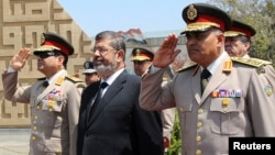 Egypt's President Mohamed Morsi (C) stands after laying a wreath during his visit to the tomb of former President Anwar al-Sadat and the Tomb of the Unknown Soldier during the commemoration of Sinai Liberation Day in Cairo, April 24, 2013.