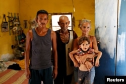 Zulay Pulgar, 43, holds her son Emmanuel, 4, next to her husband Maikel Cuauro, 30, and her father Juan Pulgar, 73, while they pose for a portrait in their house in Punto Fijo, Venezuela, Nov. 17, 2016.